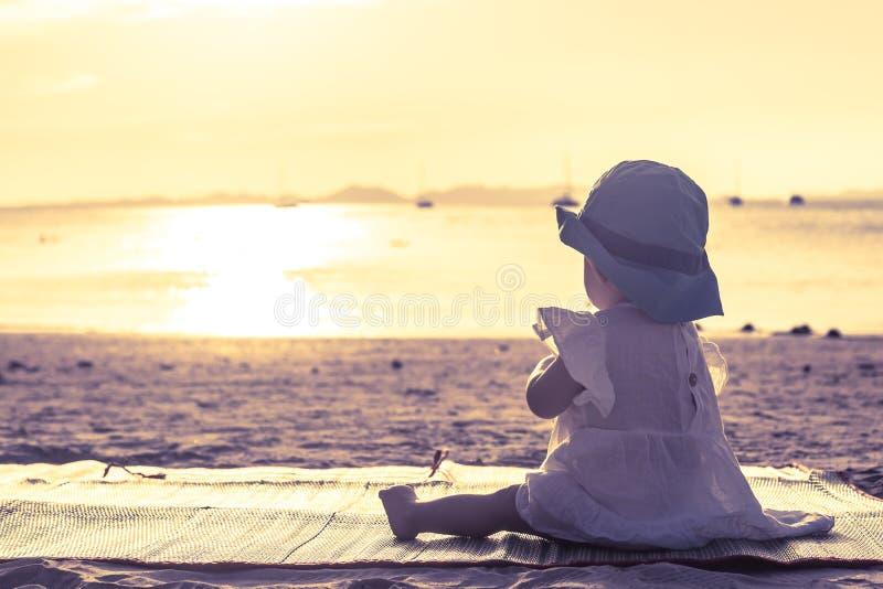 女婴坐热带海滩和享受金黄日落 免版税图库摄影
