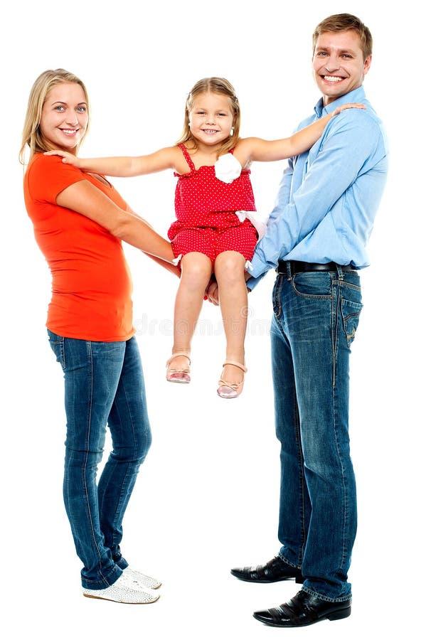 女婴坐被伸出的胳膊 免版税图库摄影