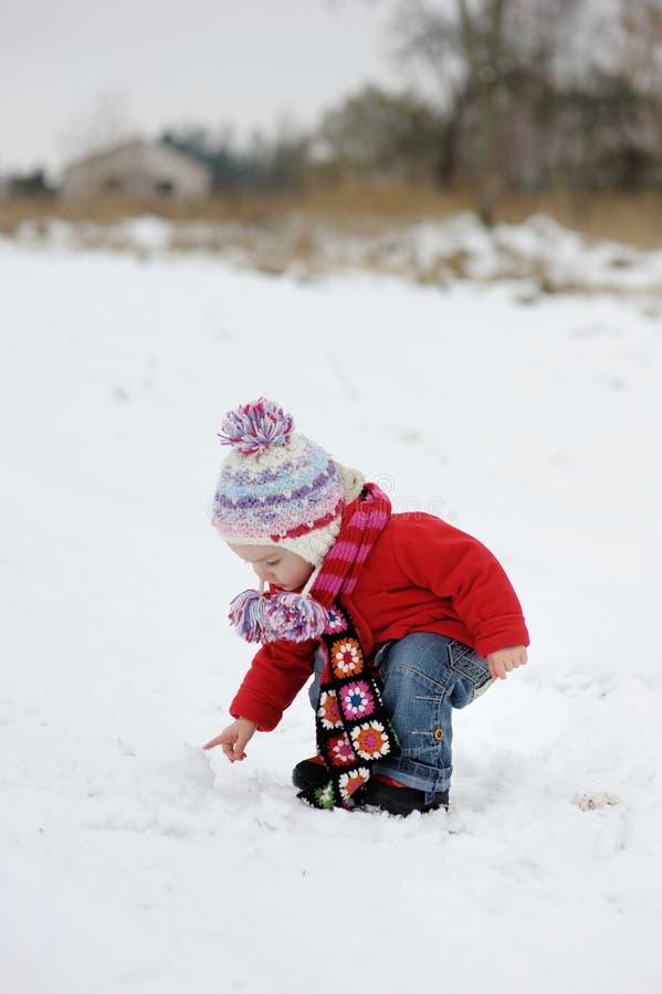女婴少许雪球感人的冬天 免版税库存图片