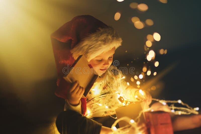 女婴打开的圣诞礼物 免版税库存照片