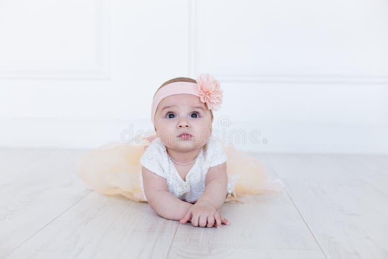 女婴沿与好奇和想知道的神色的地板爬行在她的面孔 水平的射击 逗人喜爱的6个月女孩 库存图片