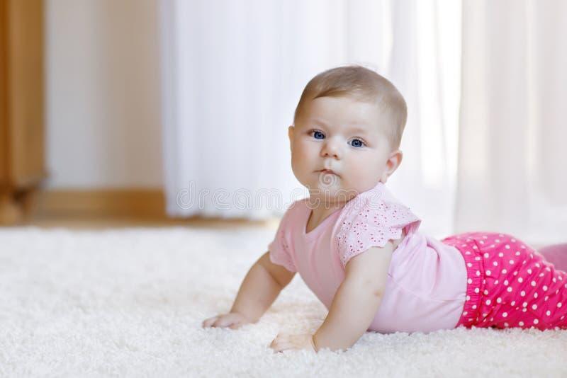 女婴画象在白色晴朗的卧室 学会爬行的婴儿 库存图片