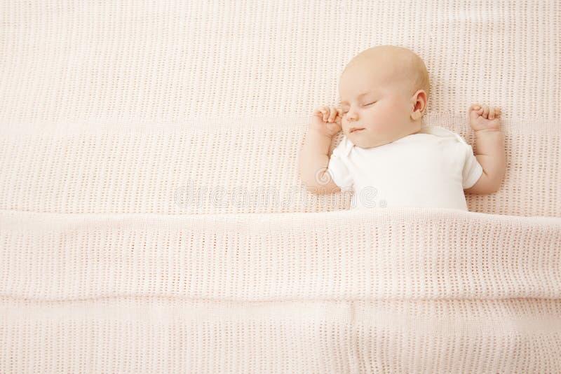 女婴睡眠在床,婴儿被盖的被编织的毯子上 免版税库存照片