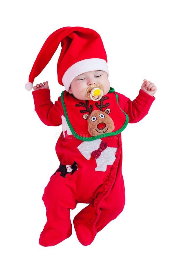 女婴睡觉或睡着与安慰者或假,红色onesie,鲁道夫驯鹿围嘴,圣诞节的圣诞老人帽子 库存照片