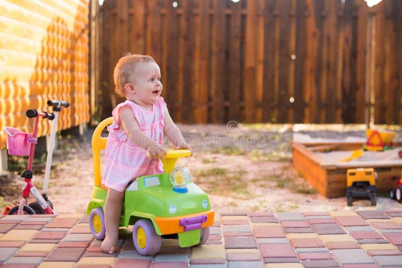 女婴骑马玩具汽车在庭院,童年的概念里 库存照片