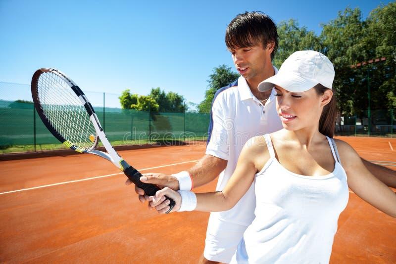 女子和男性网球辅导员实践 免版税库存图片