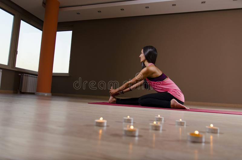 女子在家舒展的和实践的瑜伽 免版税库存图片