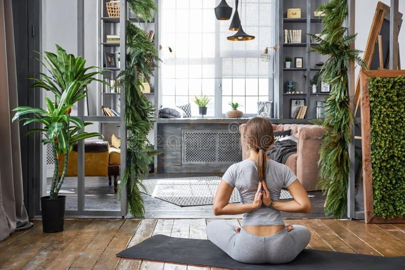 女子实践的先进的瑜伽在客厅在家 一系列的瑜伽姿势 免版税库存照片