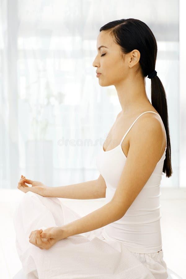 女子实践的瑜伽侧视图  免版税库存图片