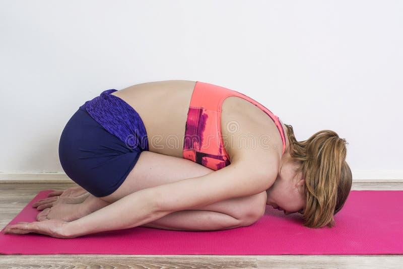 女子实践的瑜伽在家 图库摄影