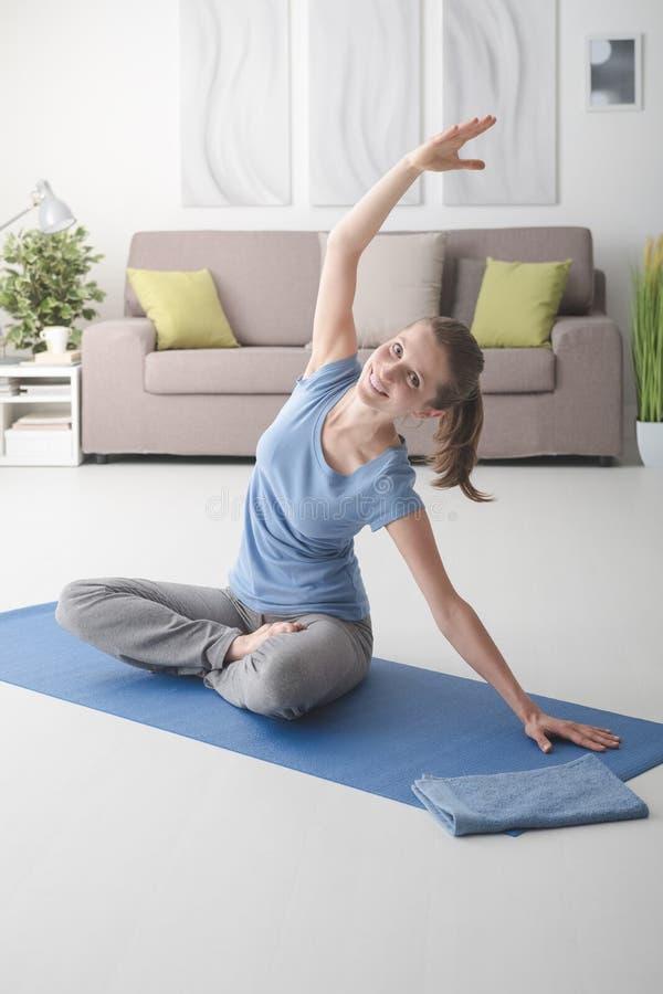 女子实践的瑜伽在家 免版税图库摄影