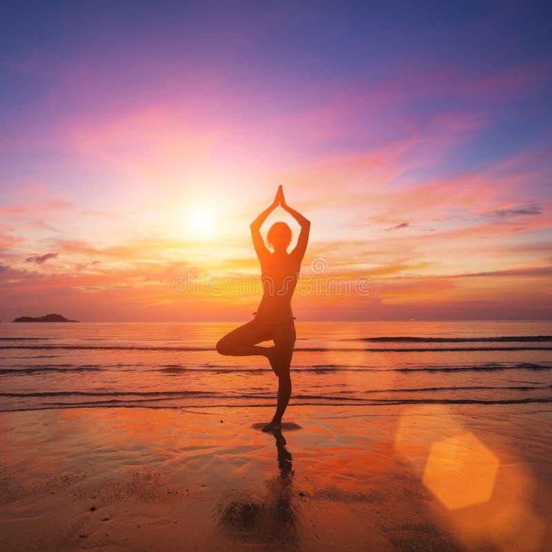 女子实践的瑜伽的剪影在超现实主义的日落的光芒的在海边 免版税库存照片