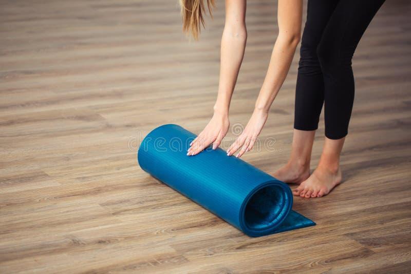 女子实践的瑜伽,为锻炼,展开的或者滚动的瑜伽席子做准备 库存图片