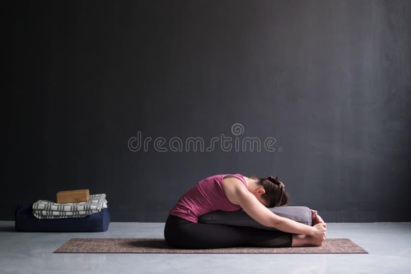 女子实践的瑜伽,做供以座位的向前弯姿势,使用承梁 免版税库存图片