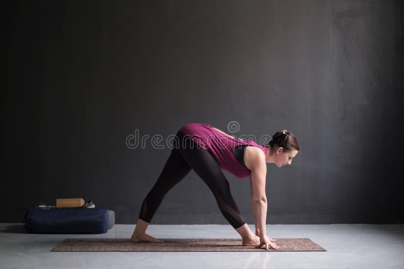 女子实践的瑜伽,做半金字塔或Parshvottanasana 免版税库存图片
