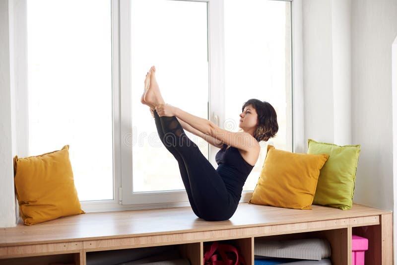 女子实践的瑜伽,坐在小船姿势锻炼,Paripurna Navasana,锻炼,佩带的黑运动服,全长 库存图片