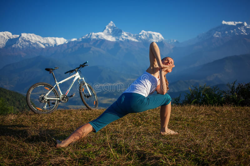 女子实践的瑜伽,放松在乘坐以后骑自行车 库存图片