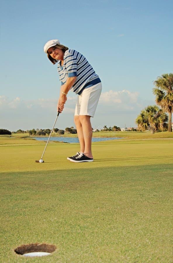 女子打高尔夫球 库存图片