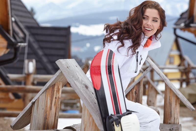 女子挡雪板 蓝色分行休息日霜谎言天空雪结构树冬天 snobord的美丽的女孩 免版税库存图片