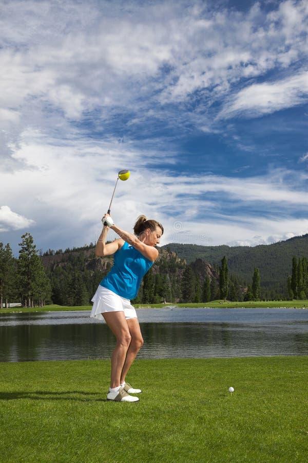 女子摇摆的高尔夫俱乐部 库存照片