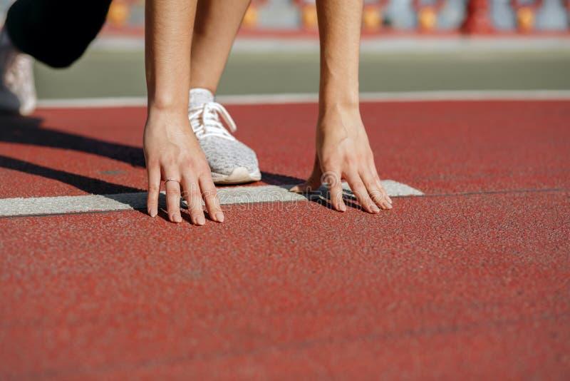 女子运动员在开始状态准备好种族 空的温泉 免版税库存照片
