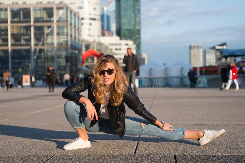 女子运动员或舞蹈家分裂腿在巴黎,法国 有长的头发的肉欲的妇女在太阳镜和牛仔裤,时尚 瑜伽, pilates, 免版税库存图片