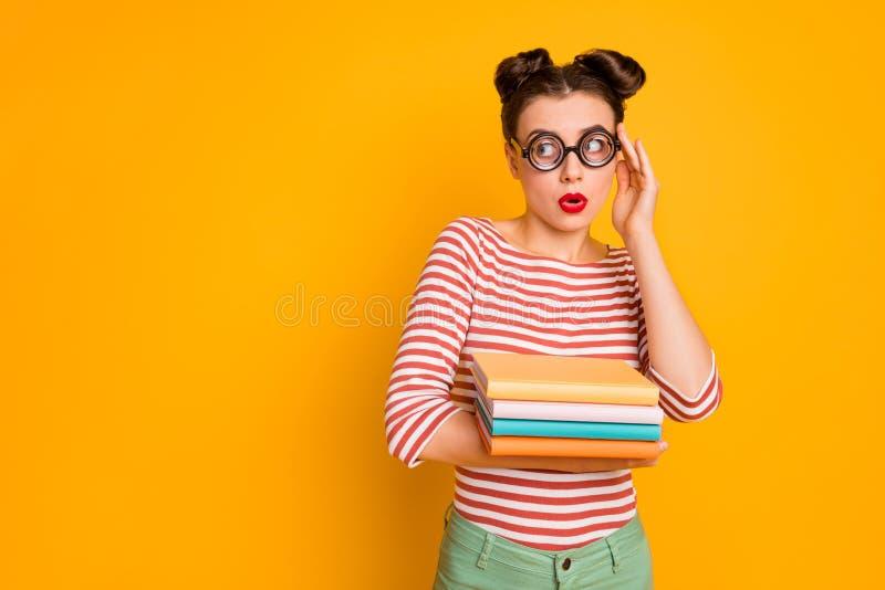 女学生手持许多书的照片,看起来像是空空如也,吓得穿怪人书呆子眼镜的红白条纹衬衫 库存照片