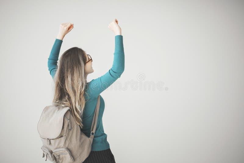 女学生胳膊上升了与在灰色背景的背包 免版税库存图片