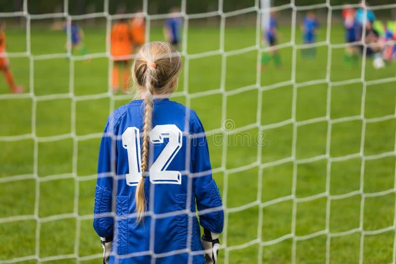 女孩'足球冠军配比 女孩足球守门员 少女站立在目标的橄榄球守门员 青年橄榄球队 库存图片