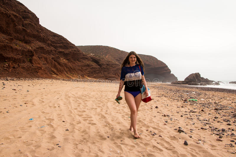 女孩、海滩和海在多云天 免版税库存图片