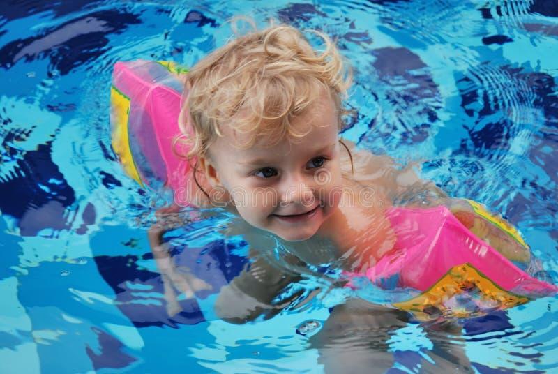 女孩一点池游泳 免版税库存图片