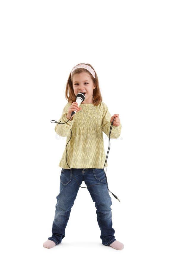 女孩一点话筒唱歌 免版税库存图片