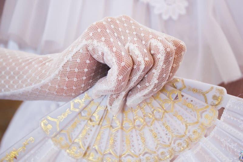 女孩一件豪华的白色礼服的和与美丽的手爱好者的白色手套的 免版税库存照片