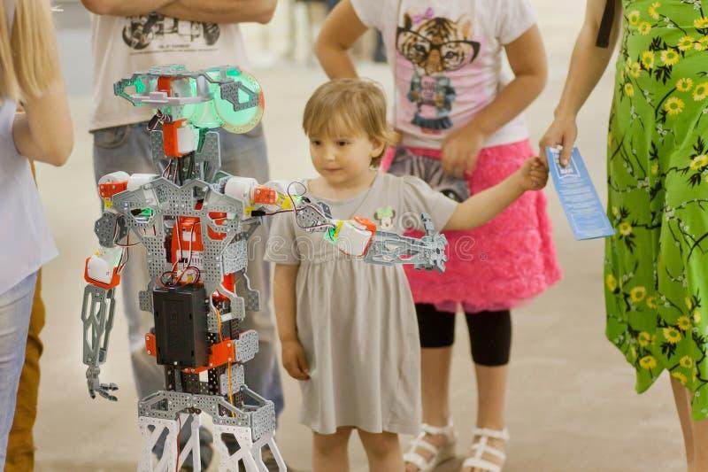 女孩与一个机械机器人回面在年轻技术员设计师的陈列 库存照片