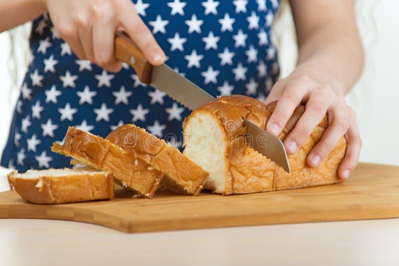 女孩与刀子的裁减面包 图库摄影