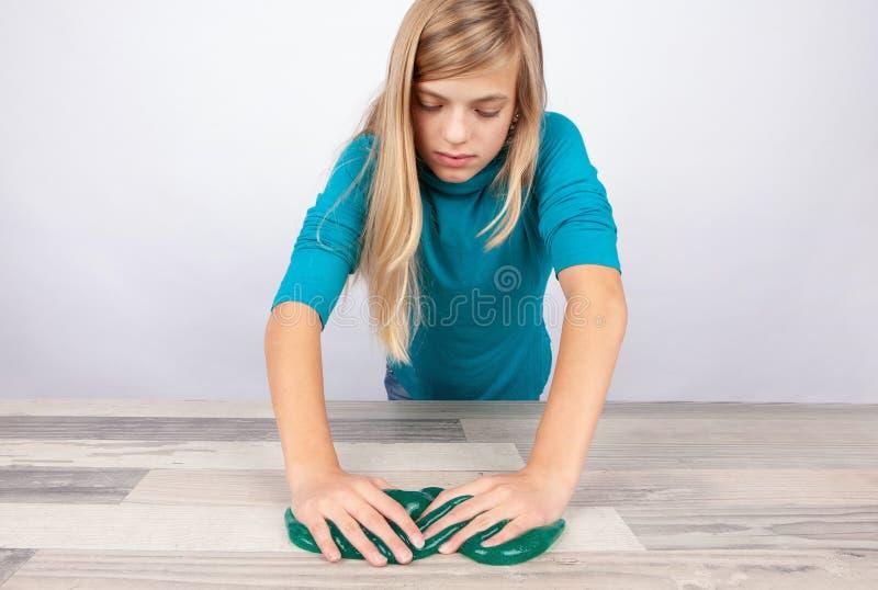 女孩与在桌上的软泥一起使用 免版税库存图片