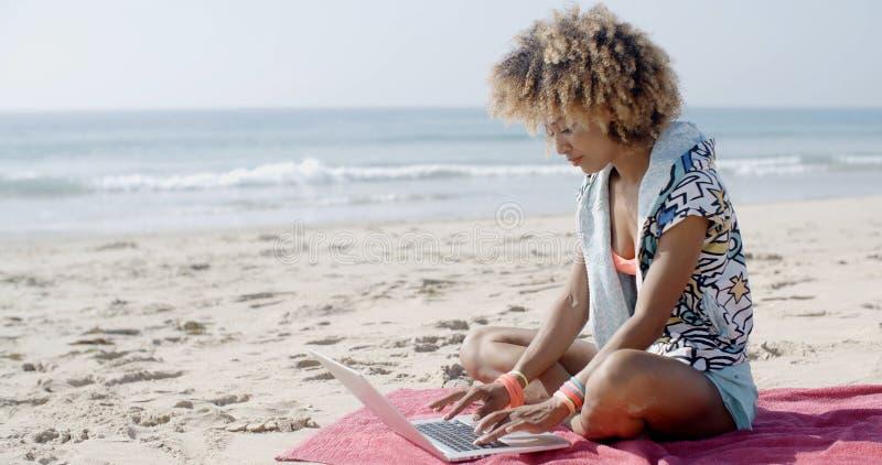 女孩与在沙子海滩的膝上型计算机一起使用 免版税库存照片
