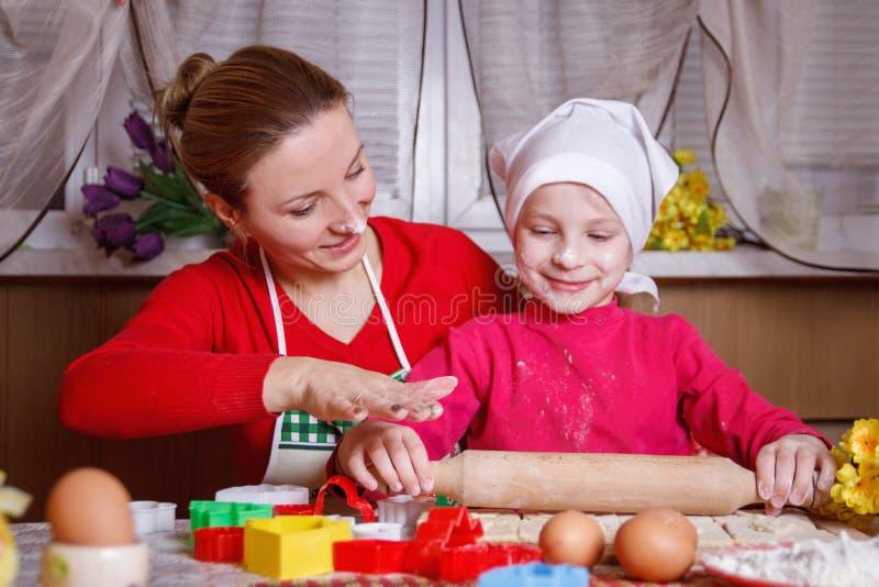 女孩与她的母亲的辗压面团bisquit的 免版税库存照片