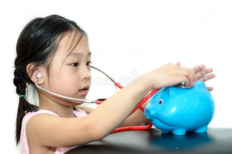 女孩与存钱罐的医生治疗,金钱概念 免版税库存照片