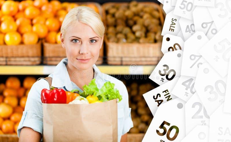 女孩与新鲜蔬菜的手袋 免版税图库摄影