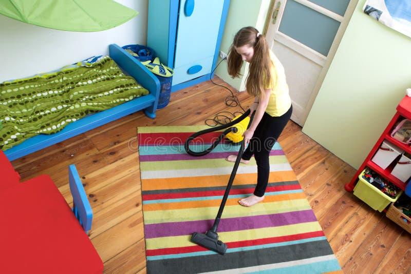女孩与真空吸尘器的清洁地板 免版税图库摄影