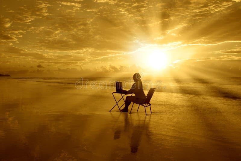 女孩与膝上型计算机在日落在这海滩 免版税库存照片