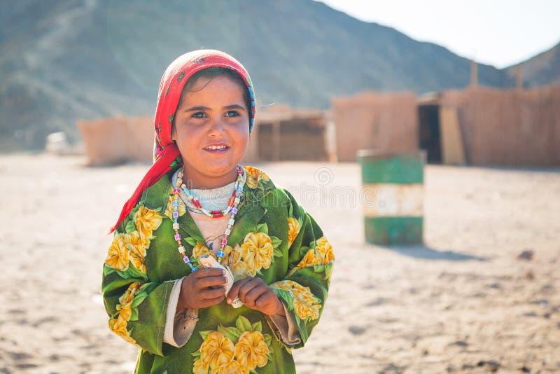 女孩与骆驼一起使用在沙漠的流浪的村庄 库存图片