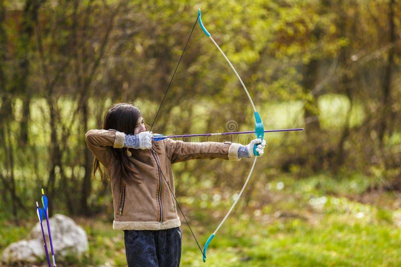 女孩与他的弓的射手射击 免版税库存照片