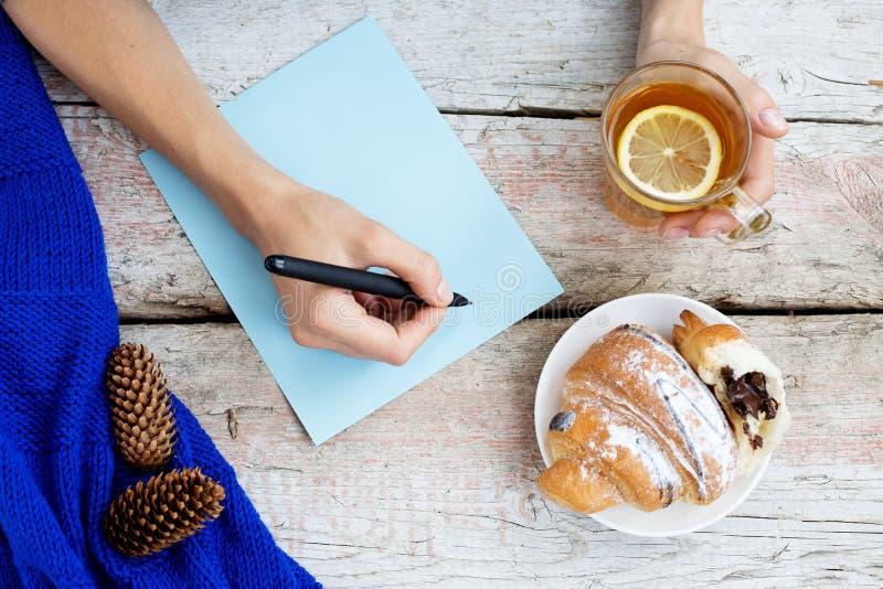 女孩为将来写着计划 热的茶和新月形面包 库存照片