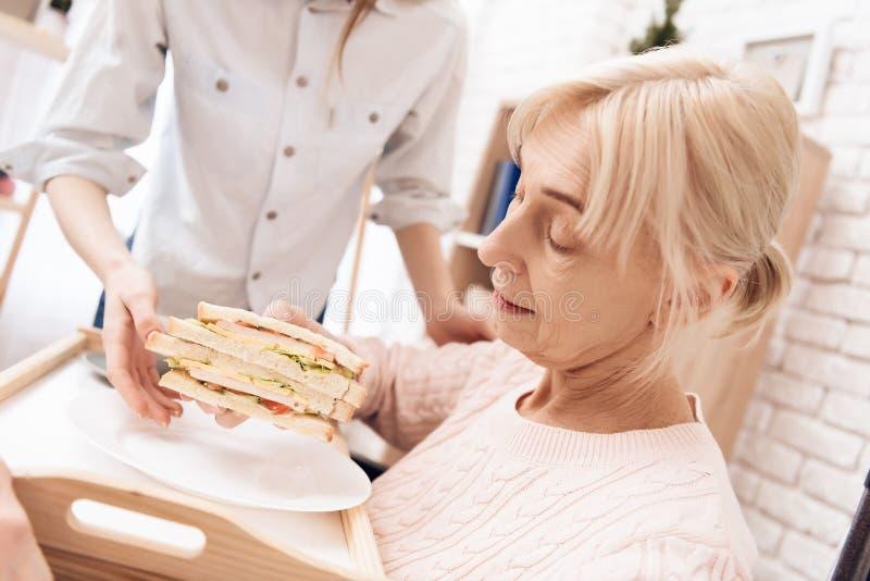 女孩为年长妇女在家是有同情心的 女孩带来在盘子的早餐 妇女吃着sandwitch 免版税库存照片