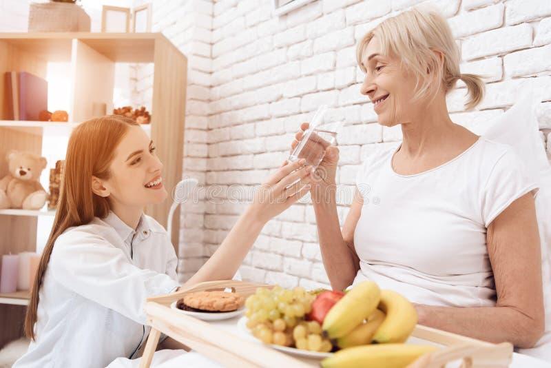 女孩为年长妇女在家是有同情心的 女孩带来在盘子的早餐 妇女是饮用水 免版税库存图片