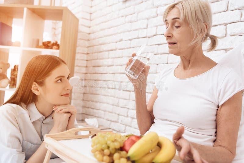 女孩为年长妇女在家是有同情心的 女孩带来在盘子的早餐 妇女是饮用水 免版税图库摄影