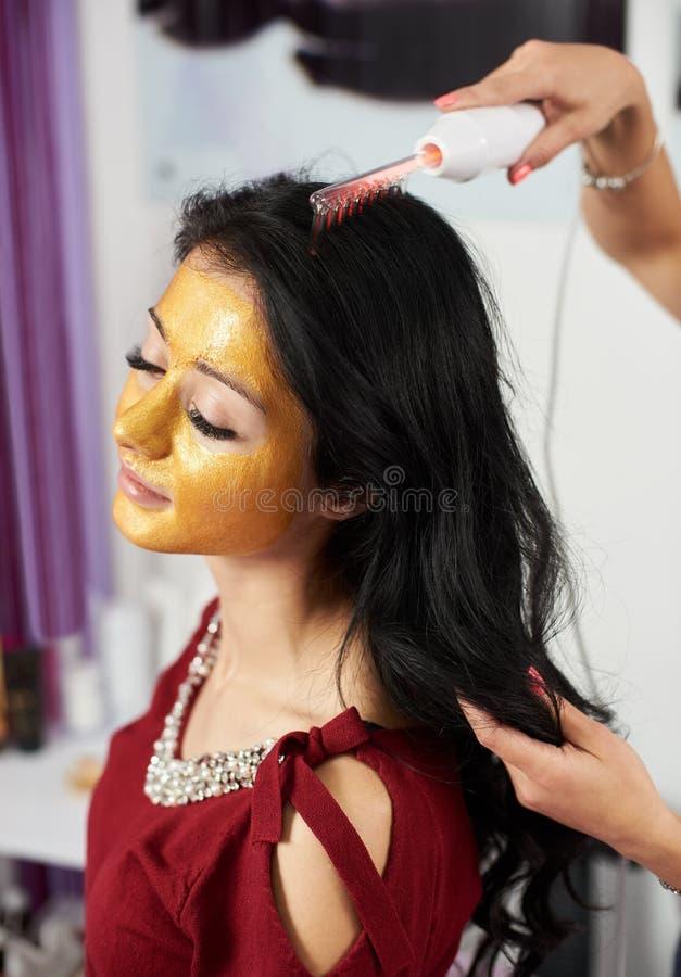 女孩为按摩头` s皮肤使用darsonval在沙龙 特写镜头 免版税库存照片