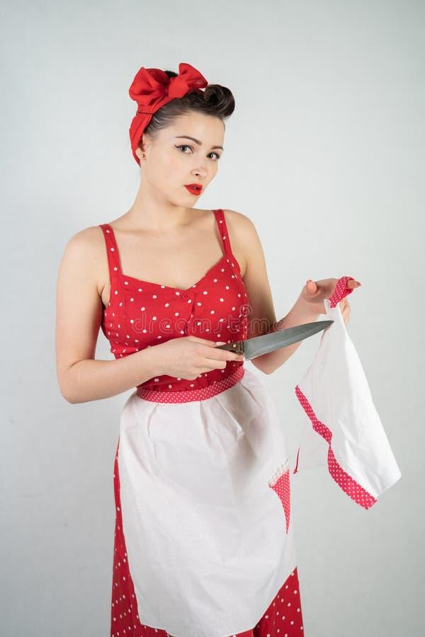 女孩主妇的危险别针红色葡萄酒圆点礼服的在她的手上站立与一把巨大的厨刀和愤怒高兴 免版税库存照片